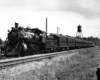 Steam locomotive with five passenger cars by semaphore signal and water tower