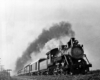 Steam locomotive with five car passenger train at speed