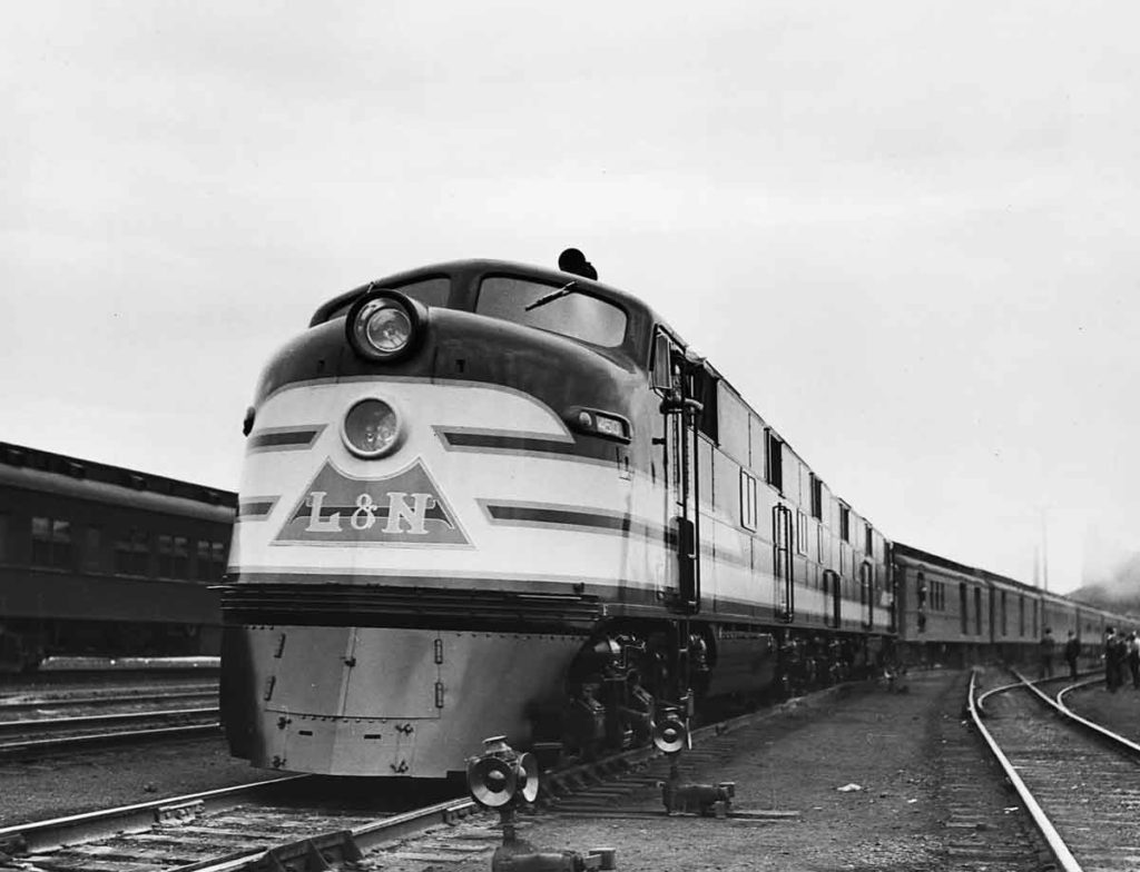 A black and white photo of a train stopped at a station