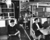 A black and white picture of people sitting and reading or playing cards on a train