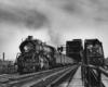 A black and white photo of a train exiting a bridge