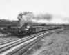 A black and white photo of a train turning a corner with smoke coming out of its chimney