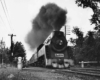 A black and white photo of a train with big black smoke coming out of its chimney