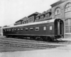A black and white photo of a sleeping car parked outside a building