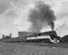 A black and white photo of a train with black smoke coming out of its chimney as it passes through a city