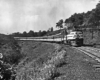 A black and white photo of a train turning a corner in a grassy area