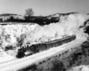 a steam passenger train rounding a curve on a winter day