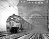 a diesel passenger train crossing a bridge on a snowy day
