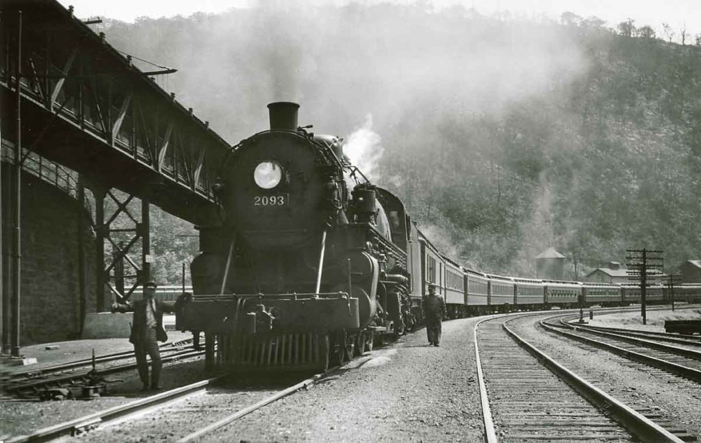 A black and white photo of a conductor posing next to a locomotive