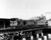 A black and white photo of a locomotive crossing a bridge