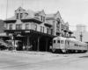 A black and white photo of a train outside a  train station