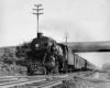 A black and white locomotive passing underneath a bridge