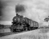 A black and white photo of a locomotive with black smoke coming out of a chimney