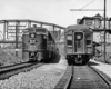 A black and white photo of two trains passing eachother on the tracks