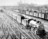 a steam engine pulling passenger cars in a rail yard