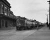 a diesel pulling passenger cars through a town
