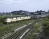 Two diesel electric locomotives haul a passenger train.