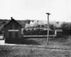 a steam passenger train pulling into a depot