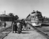 a group of passengers waiting to board a diesel passenger train