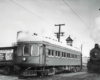 A passenger car next to a steam locomotive