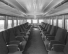 A black and white photo of the inside of a passenger car
