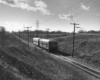 A black and white photo of a passenger train rolling down tracks near a hill