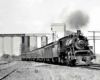 Steam locomotive with passenger on curve in front of silos