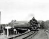 Steam locomotive with passenger train on curve on bridge