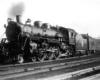 Steam locomotive with passenger train on curve under bridge