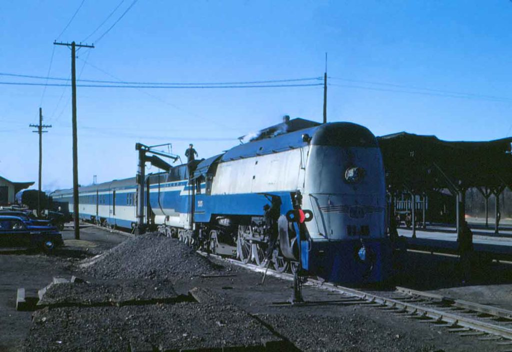 A blue and white train with two workers working on it