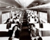 A  black and white photo of passengers sitting in a train