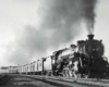 A black and white photo of a train approaching a station