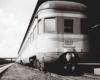 A black and white close up picture of a train parked outside a station