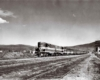 A black and white distant shot of a train passing through a rural area