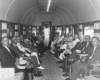 Men in suites sit in observation car
