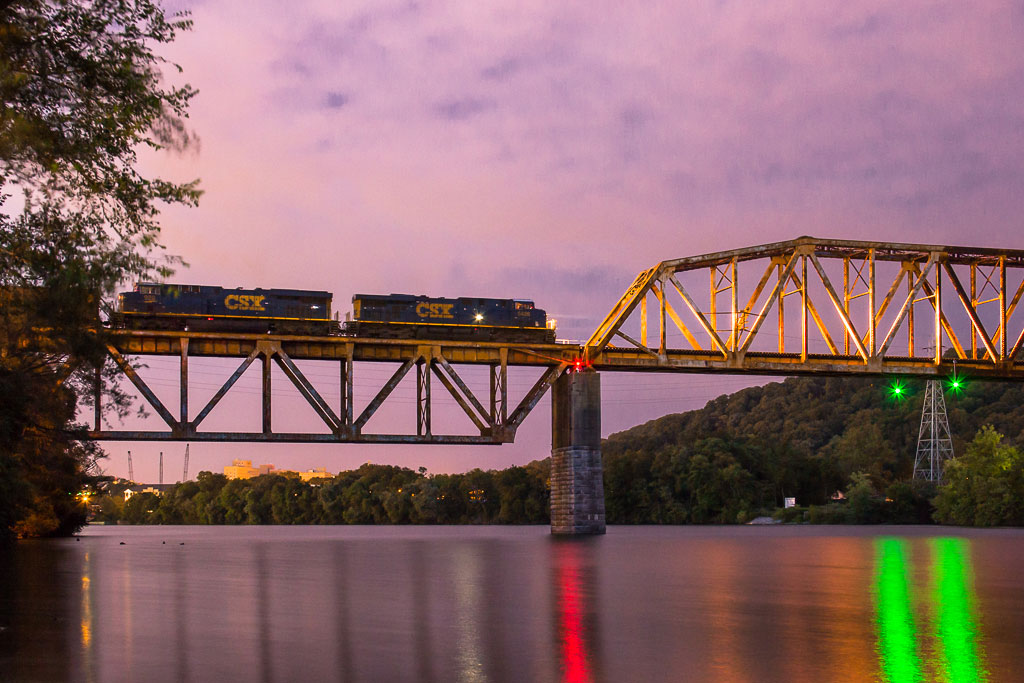 A train passing over a bridge during sunset