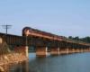 a diesel passenger train on a bridge crossing water
