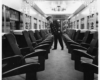 a conducter looking down the aisle on a passenger train