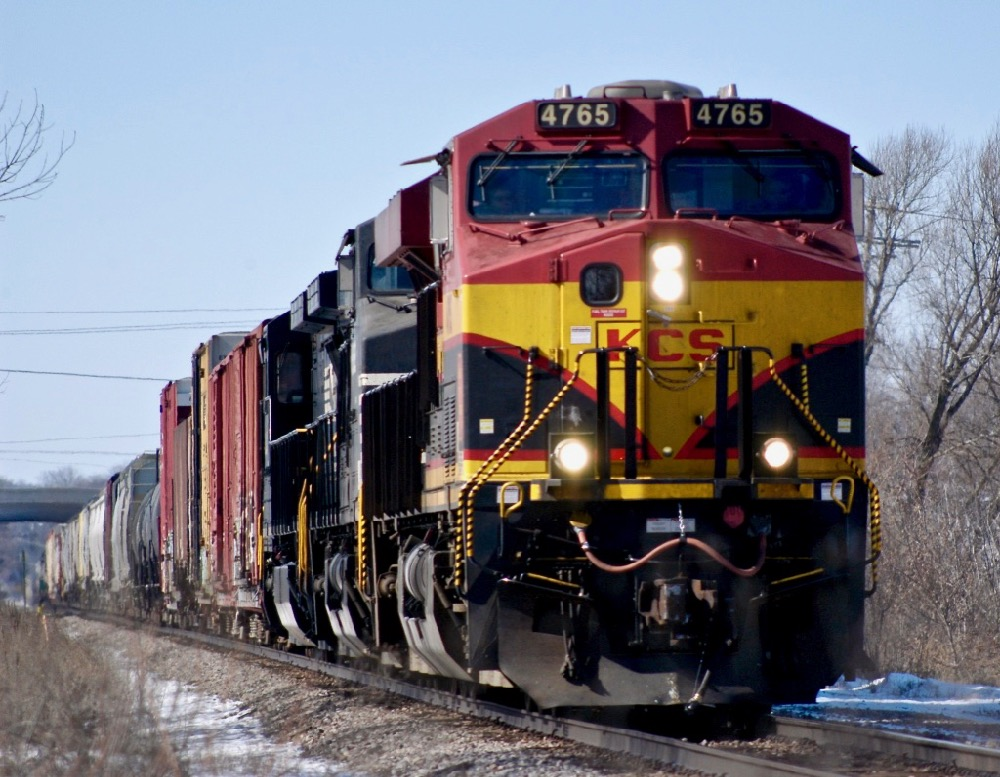 An images of a Kansas City Southern locomotive hauling a train in sunlight with blue skies in winter time.