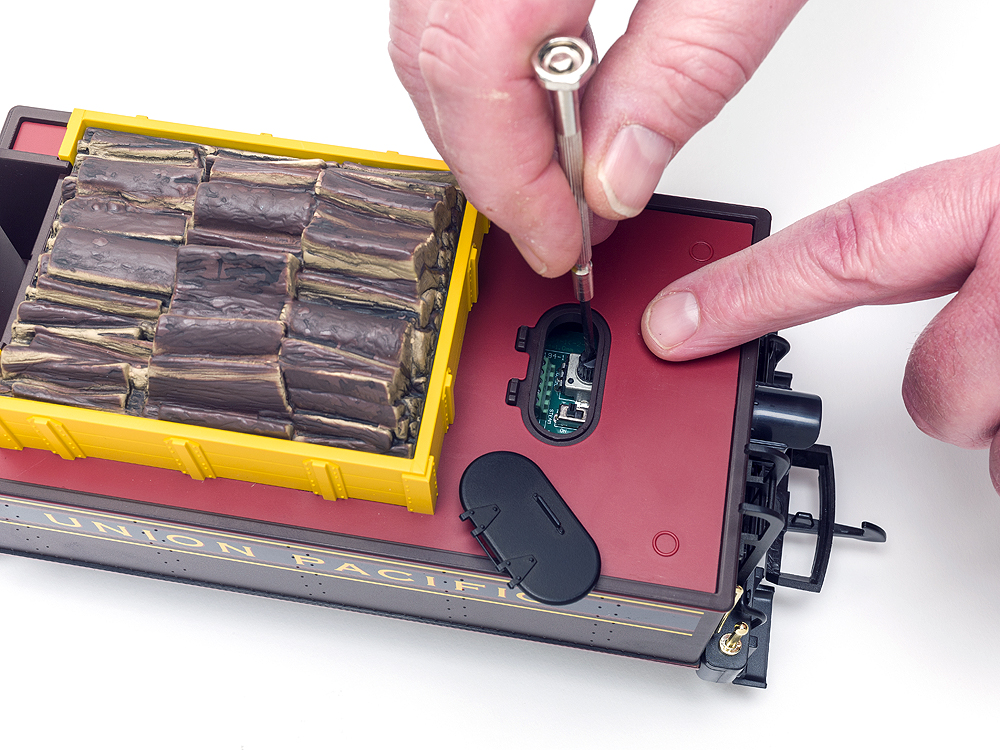 Top view of Piko mogul's tender and two hands over an open hatch, one holding a screwdriver. The tender holds the DCC circuit board.