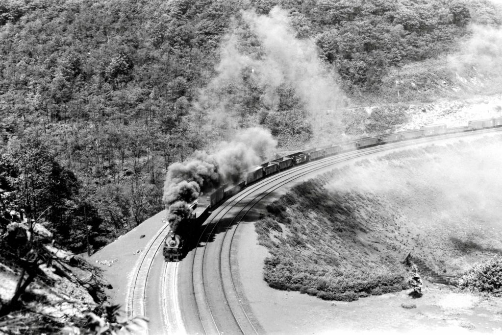 Pennsylvania Railroad class I1s 2-10-0 Decapod steam locomotive works its way around famous Horseshoe Curve with a westbound freight train in the 1940s. The train is ascending Allegheny Mountain 5 miles west of Altoona, Pennsylvania, location of the PRR's system shops.