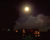 A train passing below a full moon