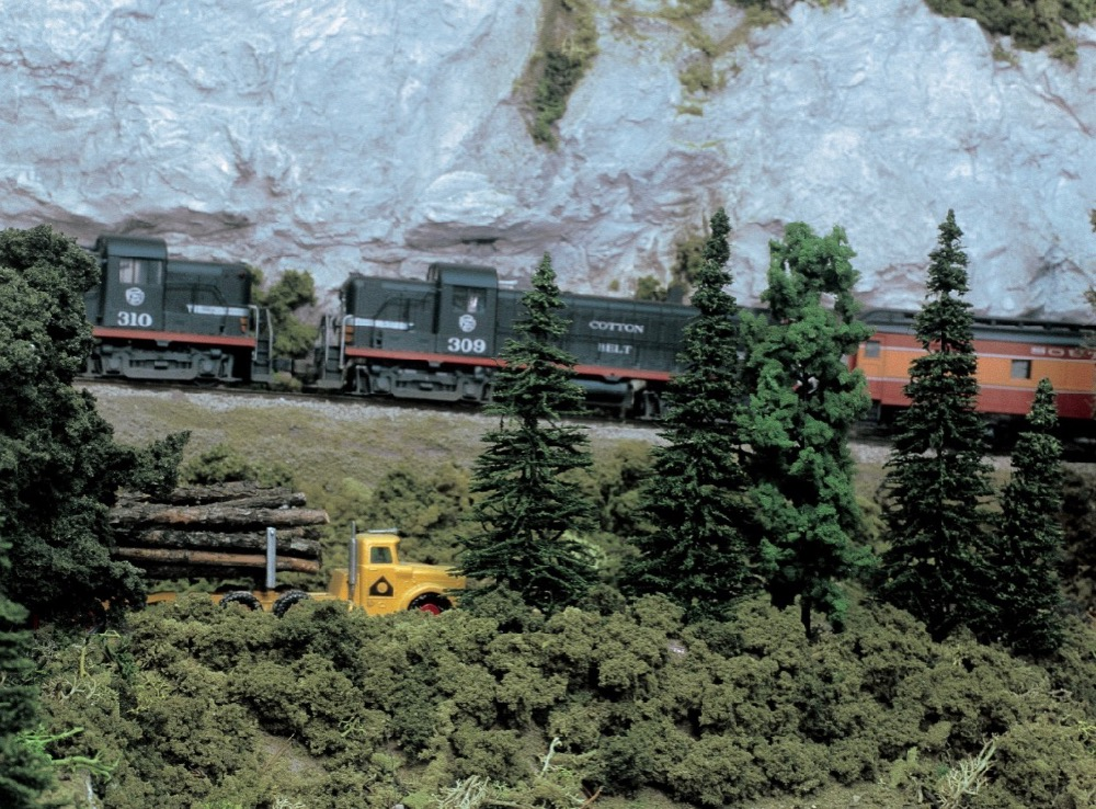 S-gauge locomotives appear to ascend uphill pulling a train to the left while a scale truck with logs moves to the right in a mountain and forest scene.