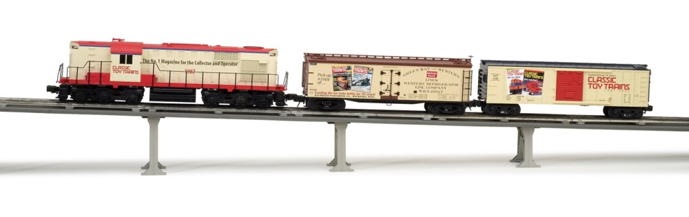 A toy train poised on a grade with tubular track.