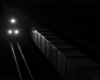 A train traveling in the dark with three headlights