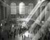 An overhead shot of people walking inside grand central station with light coming through the window