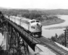 A black and white photo of F7 803 moving over a bridge