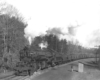 A black and white picture of someone standing on the side of the tracks watching 2-8-8-2 Mallet 740 move down the tracks with smoke coming out of its chimney