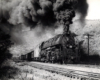 A black and white photo of locomotive 4-6-6-4 661 coming down the tracks with big black smoke coming out of its chimney