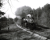 A black and white photo of Clinchfield 4-6-2 No. 154 passing by two people on the side of the tracks